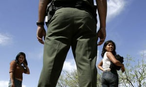 A border patrolman looks on as two Mexican women are caught trying to cross into the US