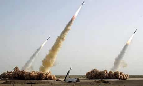 Three missiles rise into the air as a forth remains in the launcher on the ground during a test-firing in an undisclosed location in the Iranian desert
