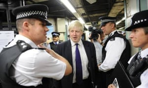 London Mayor Boris Johnson chats to police officers as they search commuters for knives in Mile End