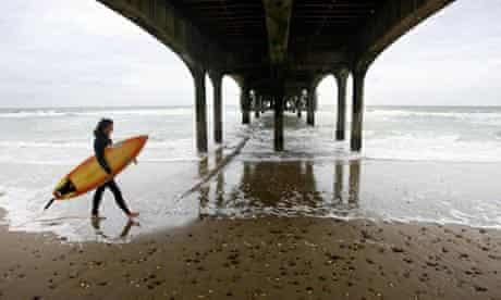 A surfer walks under Boscombe pier in Dorset