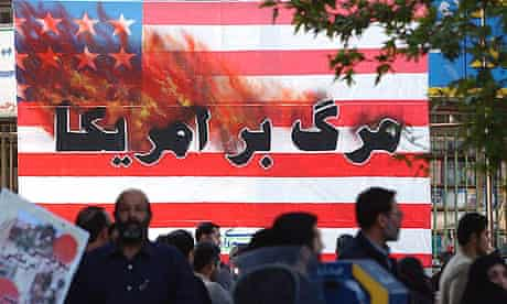 """Iranians pass a US flag with a sign reading """"Death to America"""" as they attend a rally in Tehran, in 2004."""