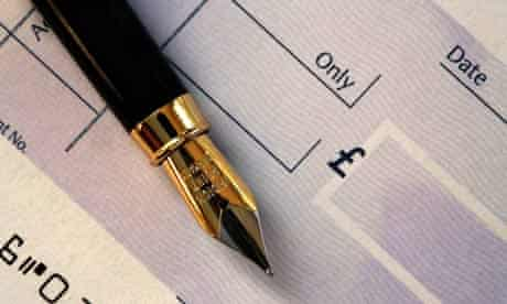 A fountain pen rests on a cheque book