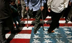 Iranian voters walk on a U.S. flag painted on the pavement as they enter a polling centre in Tehran June 24, 2005