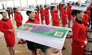 Chinese students balance books on their heads during an etiquette training class