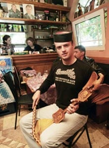 A man plays a gusle in a bar called Madhouse in Belgrade, where war crimes suspect Radovan Karadzic is now known to have frequented