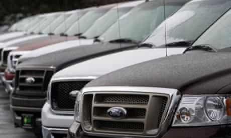 Unsold Ford pickup trucks at a dealership in Denver
