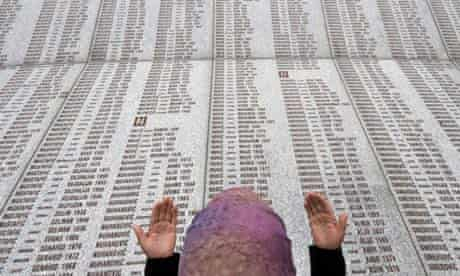 A Bosnian Muslim woman prays at the memorial wall with the names of the victims at the Potocari Memorial Center near Srebrenica
