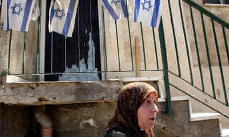 Palestinian Fawzia al-Kurd walks past a house displaying Israeli flags in the neighbourhood of occupied east Jerusalem