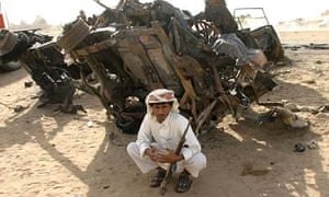 A Yemeni man sits by the wreckage of tourists' cars at the site of a suspected al-Qaeda car bomb attack in Marib in July 2007