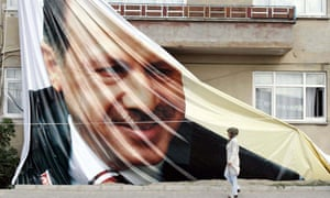 A Turkish woman walks in front of a giant poster of Turkish Prime Minister Recep Tayyip Erdogan as Turkey's constitutional court  decided whether to ban his governing party