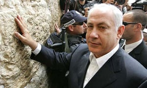 Binyamin Netanyahu surrounded by Israeli security and press as he prays at the Western Wall