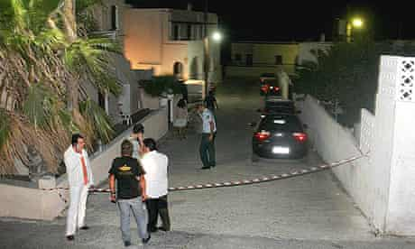 Police search for evidence outside the house where a man allegedly beheaded his girlfriend on the Greek island of Santorini.