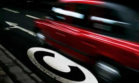 A taxi drives past a congestion charge symbol marked on the road