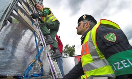 A German and an Italian officer with the joint EU force Frontex check a lorry for illegal immigrants on the Polish border.