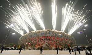 Policemen stand with their backs to the Bird's Nest Olympic stadium during the Olympic opening ceremony in Beijing, China