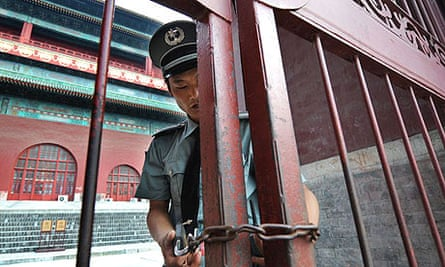 A Chinese security guard locks the gates at the Drum Tower in Beijing, following the murder of a US citizen at tourist attraction