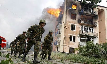 Georgian soldiers run past a building hit by bombardment in Gori, 50 miles from Tbilisi, Georgia