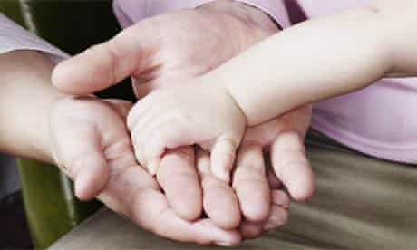 A baby holding her mother's hand
