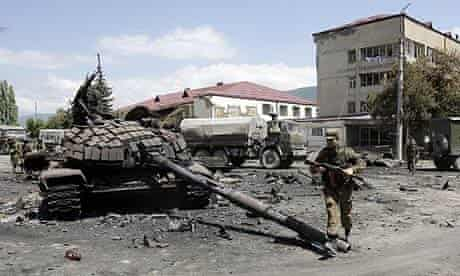 A Russian soldier walks past destroyed Georgian tanks in the South Ossetian capital of Tskhinvali