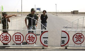 Security personnel in flak jackets stand guard at a oil field checkpoint near Kuqa in western China's Xinjiang province