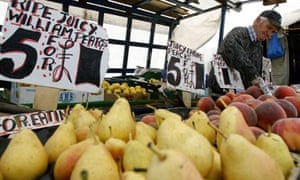 A vendor sells fruit at a market in south London