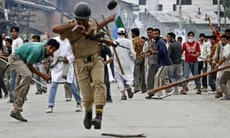 An Indian policeman is hit by an object thrown by a Kashmiri protester in Srinagar