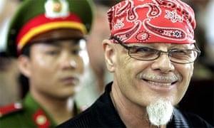 Gary Glitter smiles at journalists in a Vietnamese court before being convicted of having sex with children in March 2006
