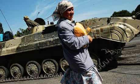 A Georgian woman carries bread past a Russian checkpoint in Gori, Georgia
