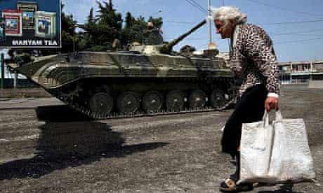 A woman passes a Russian armored vehicle in Gori, Georgia