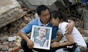 Bereaved parents with their daughter's photograph at a vigil at the Fuxin elementary school in Mianzhu county