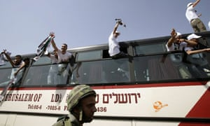 An Israeli soldier stands guard as released Palestinian prisoners gesture from inside a bus while crossing through the Beitunya checkpoint outside the West Bank city of Ramallah