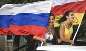 Women holding Russian and South Ossetian flags travel through Tskhinvali, South Ossetia