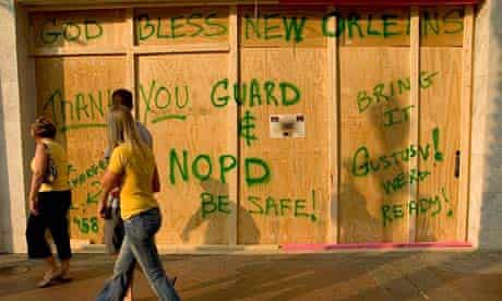 The few remaining tourists in the French Quarter pass a boarded-up business in New Orleans