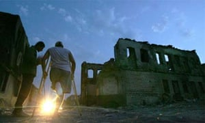 Two men stands near a destroyed building in Tskhinvali, August 30, 2008. Photograph: Viktor Drachev/AFP