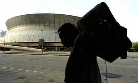 Residents of New Orleans carry their luggage past the Superdome to the City Assisted Evacuation Plan to evacuate as hurricane Gustav approaches