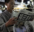 A Japanese woman reads a newspaper announcing Prime Minister Yasuo Fukuda's resignation