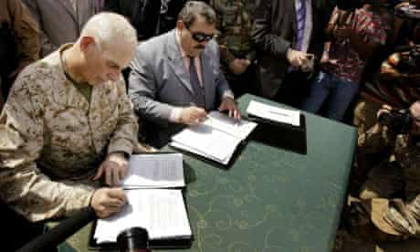 Major John Kelly and Anbar governor Mamun Sami Rasheed sign handover documents in Ramadi yesterday