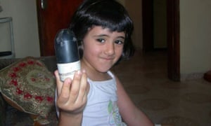 A young girl in the West Bank holds a spent missile