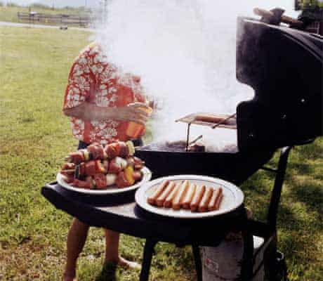 A man barbecues in a field