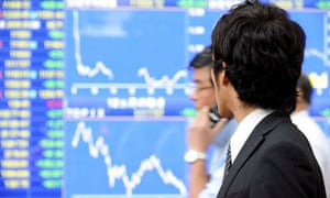 A city worker in Tokyo looks at the falling Nikkei stock index