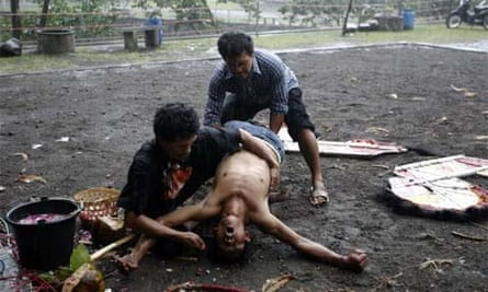 Men hold down a spectator in a trance after he watched a traditional dance, Indonesia, February 24, 2008