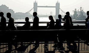 City workers walk across London Bridge on their way to their offices in the financial centre in the City of London