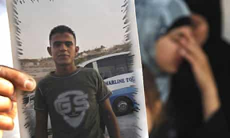 A relative of Qassem al-Mughrabi holds up a picture of the 19-year-old, whose car crashed into a patrol of Israeli soldiers