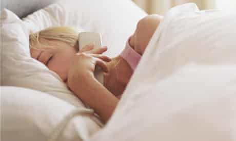 Woman lying in bed holding phone to ear