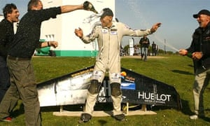 Yves Rossy is soaked in champagne by team members after landing at the South Foreland lighthouse at Dover