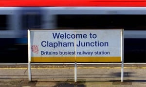 A commuter train passing the sign at Clapham Junction railway station in London