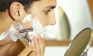 A young man shaving with a razor