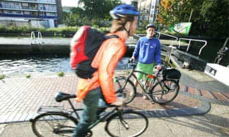 Towpath ranger  Joseph Young watches a cyclist next to Regent's canal