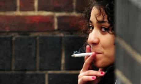 A smoker smoking a cigarette in a doorway