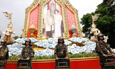Thai soldiers stand guard in front of a picture of revered King Bhumibol Adulyadej and Queen Sirikit in Bangkok